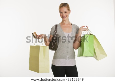 young woman with shopping bags and credit card on white seamless background - stock photo