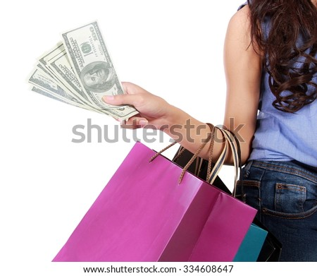 Young woman with shopping bags and money isolated on a white background