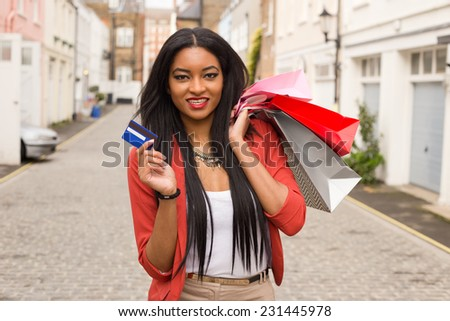 young woman with shopping bags holding a credit card. - stock photo