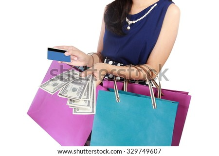Young woman with shopping bags, money, and credit card on a white background