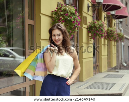 Young woman with shopping bags near shop - stock photo