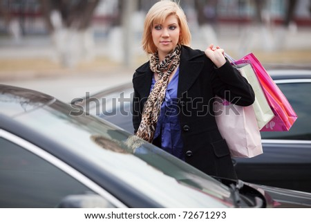 Young woman with shopping bags on a car parking - stock photo