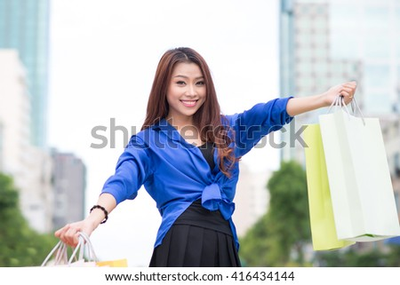 Young woman with shopping bags walking in the city - stock photo
