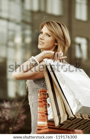 Young woman with shopping bags walking on the city street - stock photo