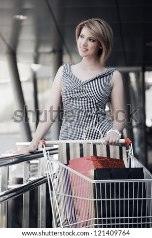 Young woman with shopping cart in a mall gallery