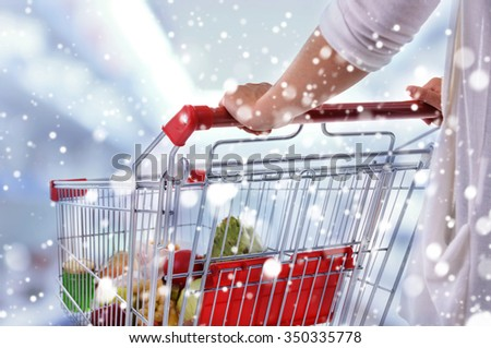 Young woman with shopping cart in store over snow effect - stock photo