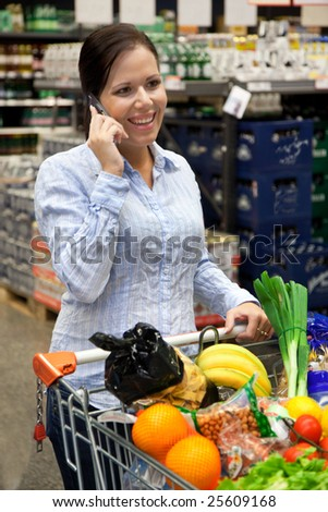 Young woman with shopping cart in the supermarket when shopping. - stock photo