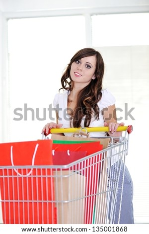 Young woman with shopping cart looking at camera