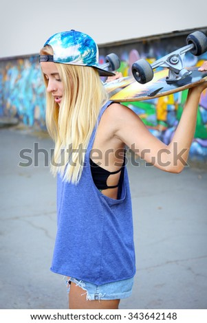 Young woman with skating board  on painted wall background