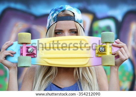 Young woman with skating board  on painted wall background - stock photo
