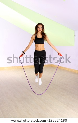 Young woman with skipping rope at gym - stock photo