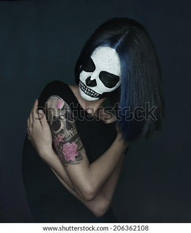 Young woman with skull make-up and skull tattoo on her shoulder. Halloween face art