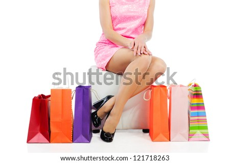 Young woman with slim legs sitting near colorful shopping bags. Isolated on white background.