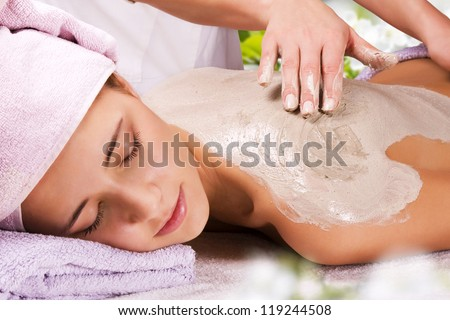 Young woman with slimming body thermal mask on her back. Spa Treatment.