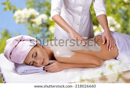 Young woman with slimming body thermal mask on her back. Spa Treatment.  - stock photo