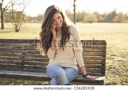 young woman with smart phone at the park - stock photo