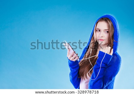 young woman with smart phone listening music. Teen stylish long hair girl in hood relaxing or learning language. Studio shot on blue. - stock photo