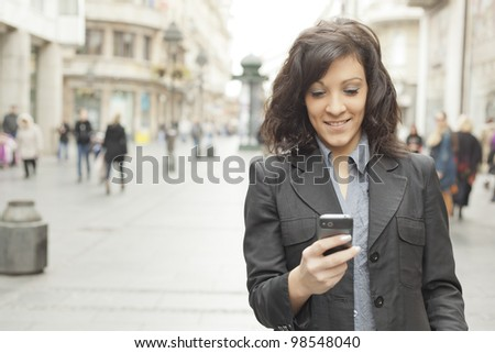 Young Woman with smartphone walking on street, downtown. In background is blurred street - stock photo