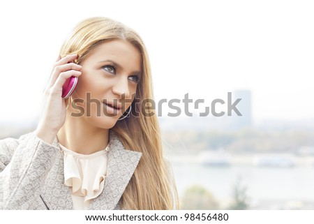 Young Woman with smartphone walking outdoor, downtown. In background is blurred city - stock photo