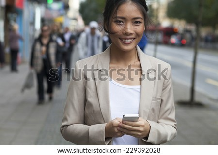 Young Woman with smile and smart phone walking on street - stock photo