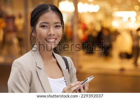 Young Woman with smile and smart phone walking on street