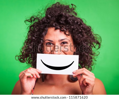 Young Woman with Smiley Emoticon on Green Background - stock photo