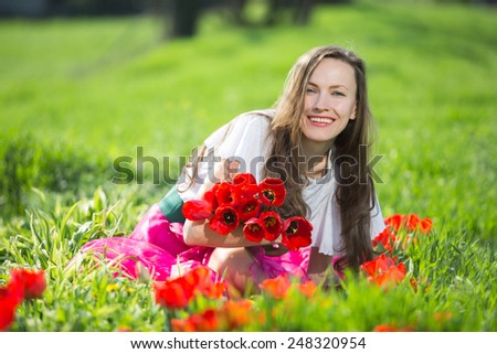 Young woman with spring flowers on a sunny spring meadow - stock photo