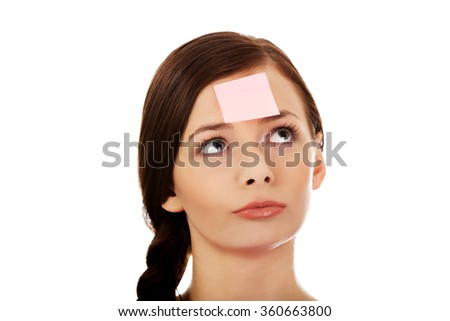 Young woman with sticky notes on forehead - stock photo