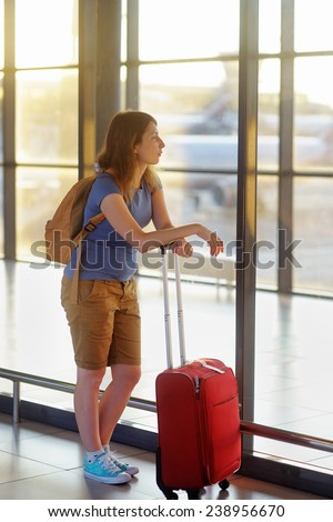 Young woman with suitcase at the airport with airplane on background