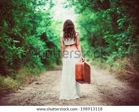 Young woman with suitcase in hand going away by a rural road - stock photo