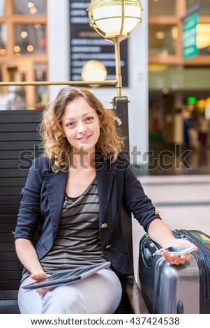 Young woman with suitcase waiting for her train inside of the train station.