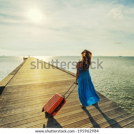 Young woman with suitcase waking on wooden pier.