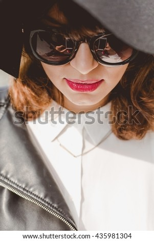 Young woman with sunglasses and big black hat