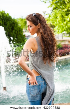 young woman with sunglasses and summer casual clothes by city fountain - stock photo