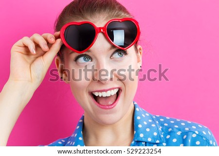 Young woman with sunglasses on a pink background