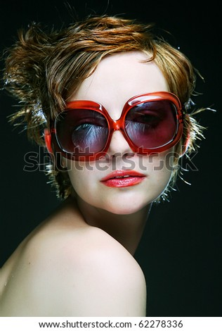 young woman with sunglasses on black background