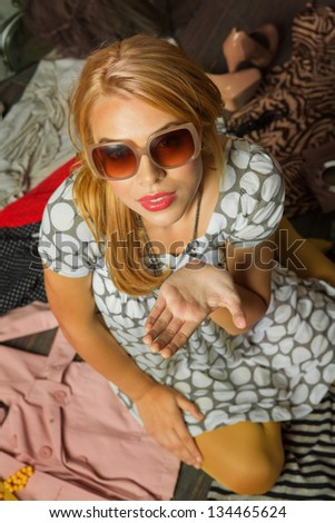young woman with sunglasses sitting in clothes and holding her hand in receiving gesture