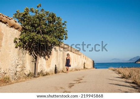 Young woman with sunglasses walking next to a wall with a tree in an empty road in a sunny day. Mediterranean sea in the background. - stock photo