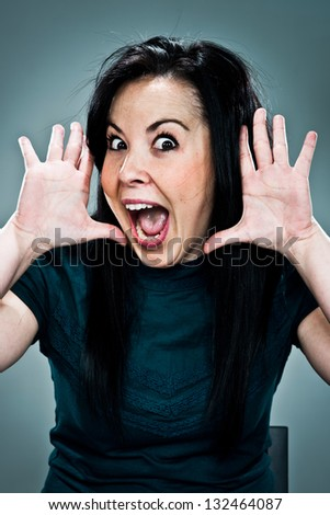 Young Woman with Surprise Expression Over a Grey Background