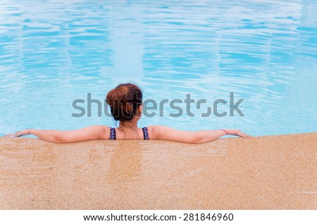 Young woman with swimsuit in swimming pool - stock photo