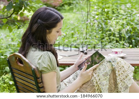 young woman with tablet PC in a garden - stock photo