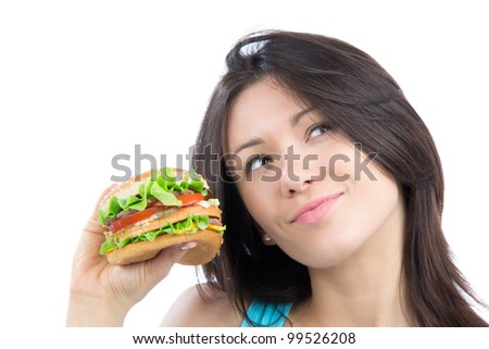 Young woman with tasty fast food unhealthy burger in hand getting ready to eat isolated on a white background. Focus on hand with hamburger. - stock photo