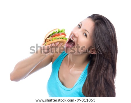 Young woman with tasty fast food unhealthy burger or hamburger in hand getting ready to eat isolated on a white background