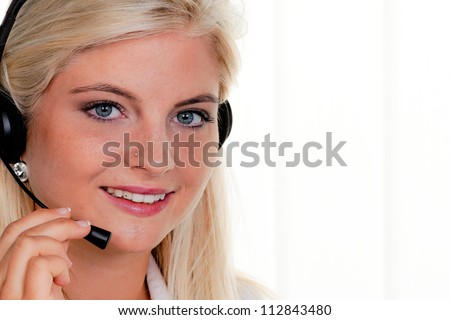 young woman with telephone headset in a call center