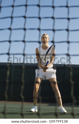Young woman with tennis racket standing behind net