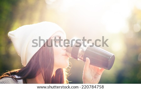 Young woman with thermos outdoor portrait in soft sunny daylight - stock photo