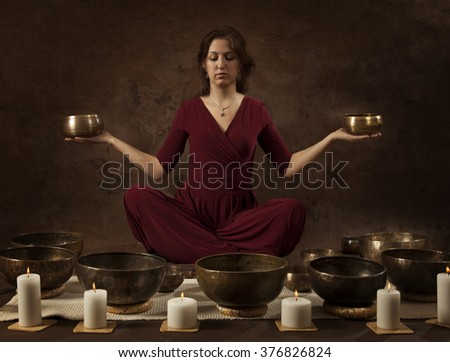 Young woman with Tibetan singing bowls in her hands in front of brown background - stock photo