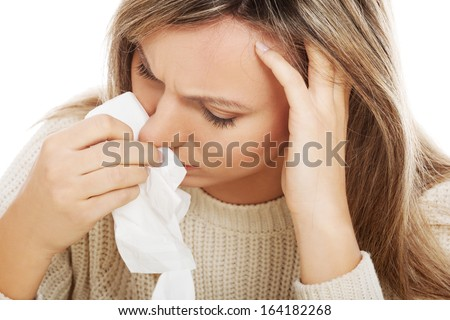 Young woman with tissues crying/ having runny nose. Isolated on white.  - stock photo