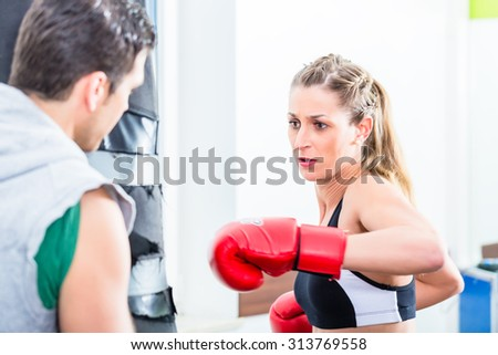 Young woman with trainer in boxing sparring hitting sandbag - stock photo