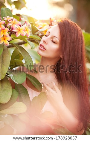 young woman with tropical flower Plumeria alba